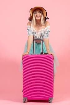 Widok z przodu młoda kobieta przygotowuje się na letnie wakacje z różową torbą na różowym tle kolor podróż samolotem w podróży odpoczynek