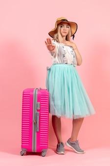 Widok z przodu młoda kobieta przygotowuje się na letnie wakacje z różową torbą na różowym tle wycieczka rejs wakacje morski samolot odpoczynku kolor