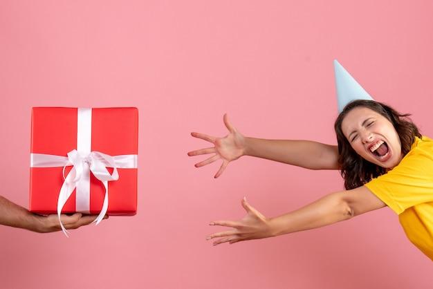 Widok z przodu młoda kobieta przyjmująca prezent od mężczyzny na różowo