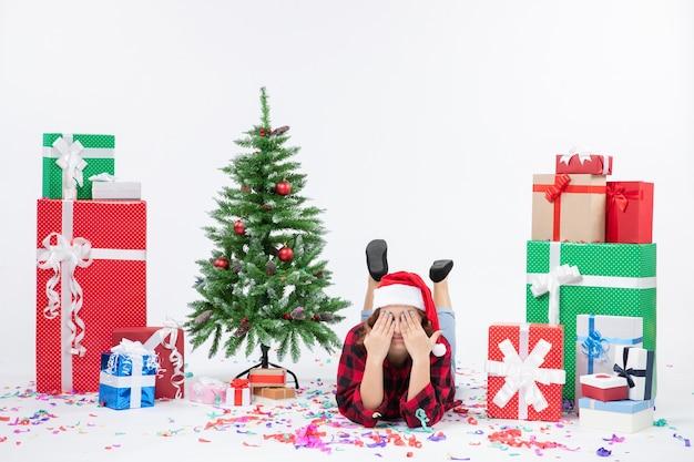 Widok z przodu młoda kobieta r. wokół prezentów świątecznych i choinki na białym tle boże narodzenie nowy rok kolor śniegu