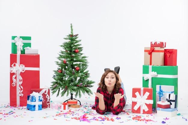 Widok z przodu młoda kobieta r. wokół prezentów świątecznych i choinki na białym tle boże narodzenie prezenty nowego roku kolor śniegu