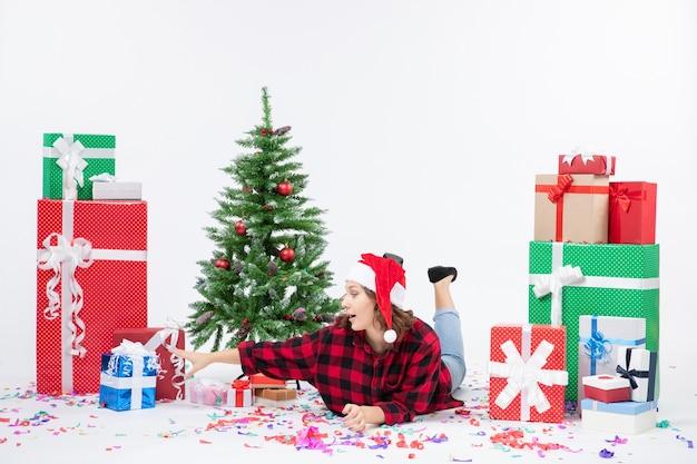 Widok z przodu młoda kobieta r. wokół prezentów świątecznych i choinki na białym tle cold woman xmas new year snow