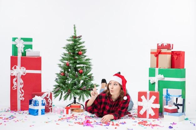 Widok z przodu młoda kobieta r. wokół prezentów świątecznych i choinki na białym tle kolor nowego roku kobieta xmas śnieg