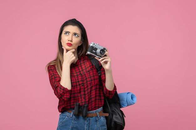 Widok z przodu młoda kobieta robi zdjęcie aparatem na jasnoróżowym tle kobieta zdjęcie koloru