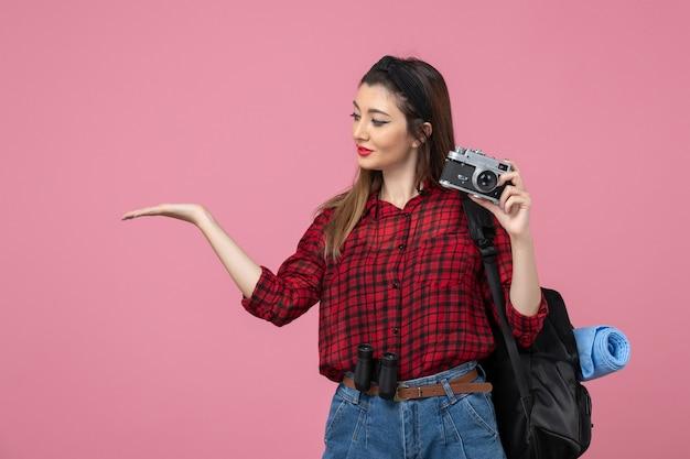 Widok z przodu młoda kobieta robi zdjęcie aparatem na różowym tle zdjęcie modelki