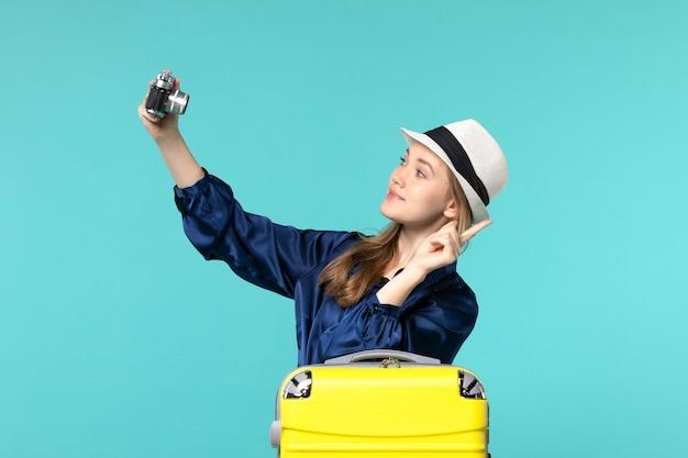 Widok z przodu młoda kobieta robienie zdjęć aparatem na niebieskim tle kobieta podróż morze podróżujący samolotem