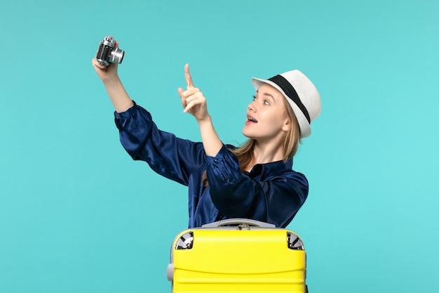 Widok z przodu młoda kobieta robienie zdjęć aparatem na niebieskim tle kobieta podróż samolotem rejsu morskiego