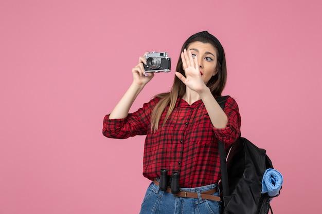 Widok z przodu młoda kobieta robienie zdjęć aparatem na różowym biurku kobieta zdjęcie koloru
