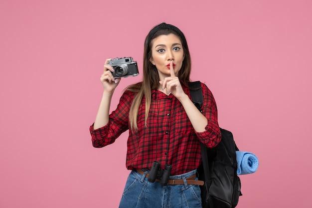 Widok z przodu młoda kobieta robienie zdjęć aparatem na różowym tle kolor zdjęcia kobiety