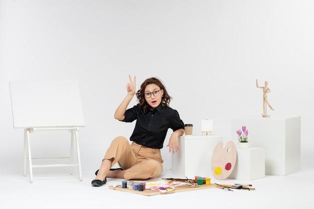 Widok z przodu młoda kobieta siedząca w pokoju z farbami chwostami i sztalugami na białym tle