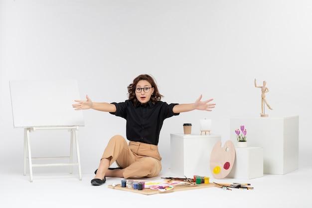 Widok z przodu młoda kobieta siedząca w pokoju z farbami sztalugowymi i frędzlami na białym tle
