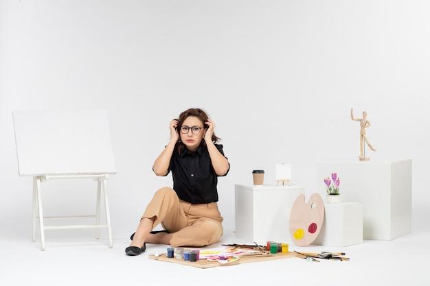Widok z przodu młoda kobieta siedząca w pokoju ze sztalugą i farbami na białej podłodze rysować obraz malarstwo artysta malarz kolor