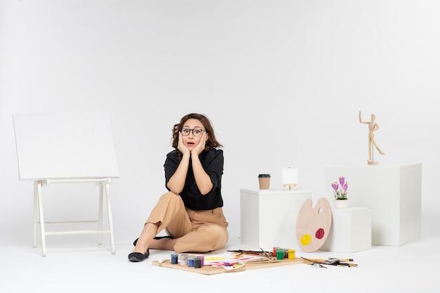 Widok z przodu młoda kobieta siedząca w pokoju ze sztalugą i farbami na białym biurku rysowanie sztuki obraz malarstwo artysta malarz kolor