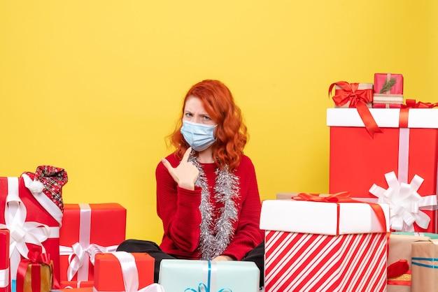 Widok z przodu młoda kobieta siedząca wokół świątecznych prezentów z maską na żółtym wirusie emocji covid - kolor nowego roku