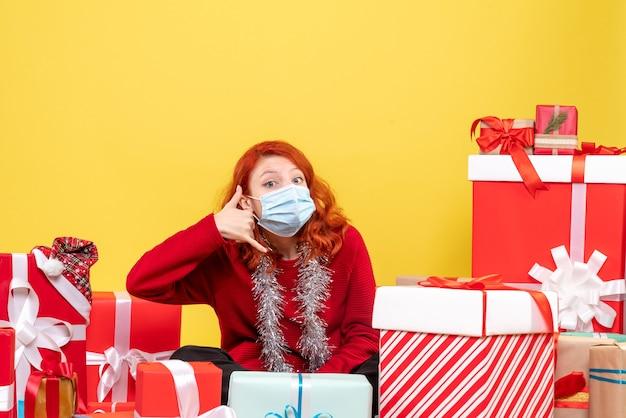 Widok z przodu młoda kobieta siedząca wokół świątecznych prezentów z maską na żółtym wirusie emocji nowego roku
