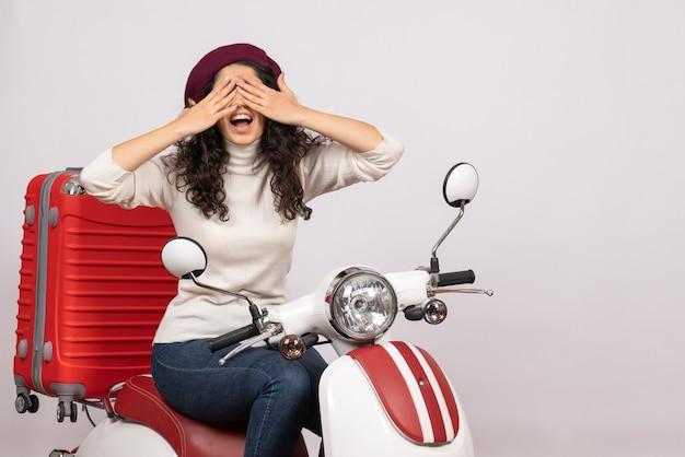Widok z przodu młoda kobieta siedzi na rowerze zakrywając twarz na białym tle kobieta pojazd prędkość wakacje motocykl droga miasto kolor