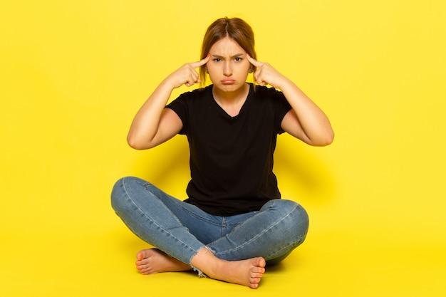 Widok z przodu młoda kobieta siedzi w czarnej koszuli i dżinsach, myśląc smutno na żółto