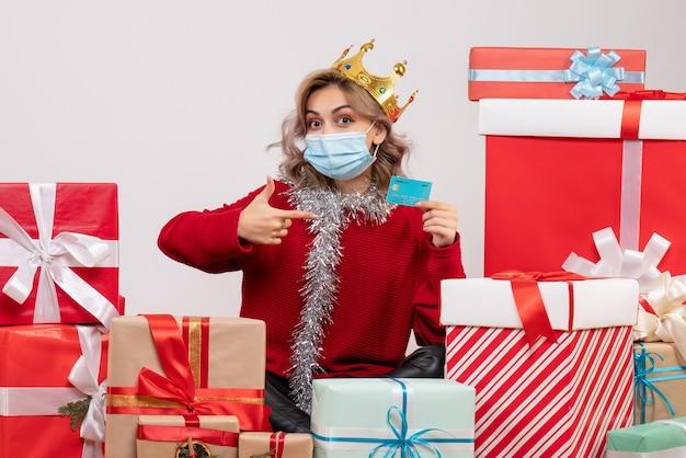 Widok z przodu młoda kobieta siedzi wokół prezentów bożonarodzeniowych trzymając kartę bankową