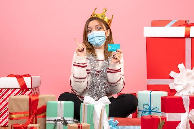 Widok z przodu młoda kobieta siedzi wokół prezentów świątecznych z kartą bankową