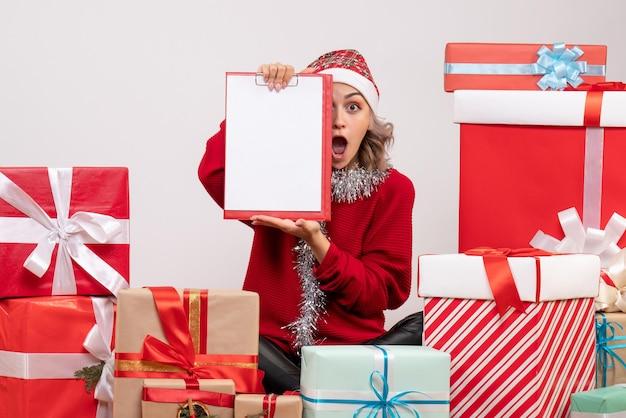 Widok z przodu młoda kobieta siedzi wokół prezentów świątecznych z notatką