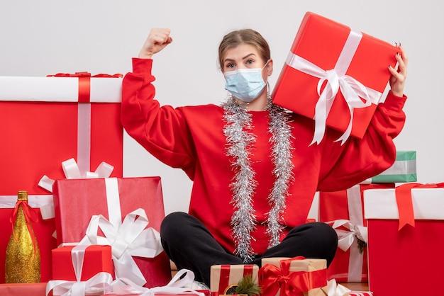 Widok z przodu młoda kobieta siedzi wokół prezentów świątecznych