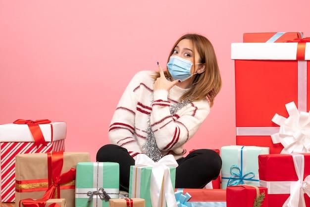 Widok z przodu młoda kobieta siedzi wokół prezentów