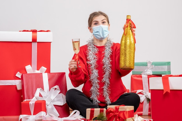 Widok z przodu młoda kobieta siedzi wokół prezenty świętuje z szampanem
