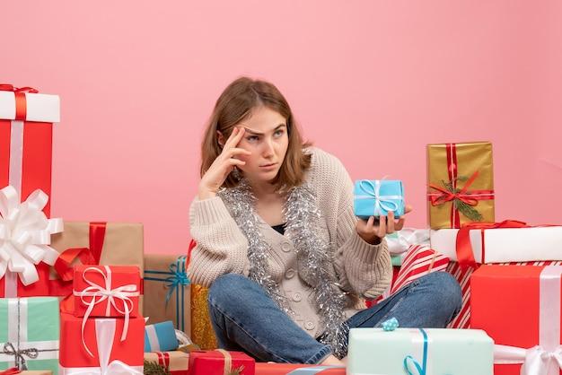 Widok z przodu młoda kobieta siedzi wokół różnych prezentów