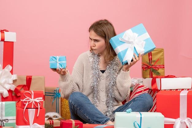 Widok z przodu młoda kobieta siedzi wokół różnych świątecznych prezentów