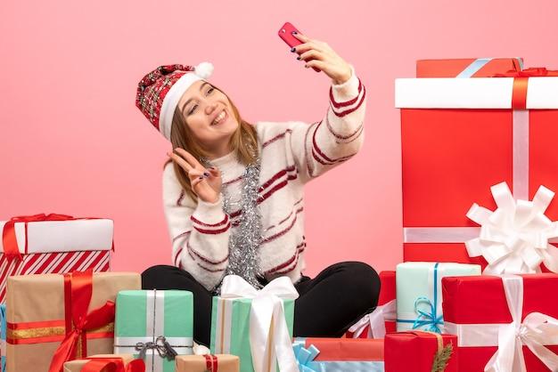 Widok z przodu młoda kobieta siedzi wokół świątecznych prezentów, biorąc selfie