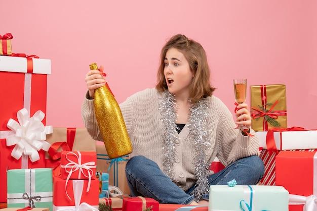 Widok z przodu młoda kobieta siedzi wokół świątecznych prezentów świętuje z szampanem