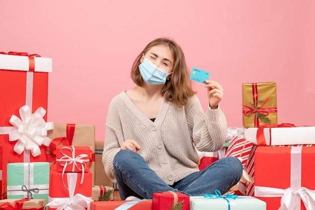 Widok z przodu młoda kobieta siedzi wokół świątecznych prezentów w masce
