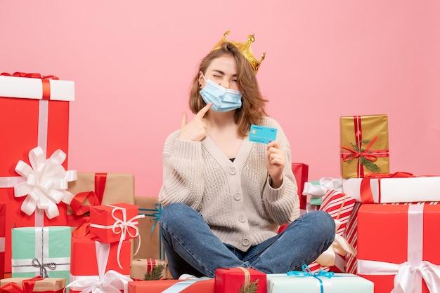 Widok z przodu młoda kobieta siedzi wokół świątecznych prezentów w sterylnej masce