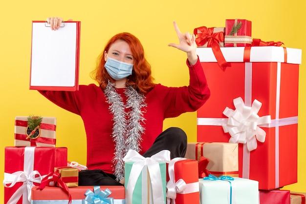 Widok z przodu młoda kobieta siedzi wokół świątecznych prezentów z notatką dotyczącą żółtego wirusa emocji covid - kolor nowego roku