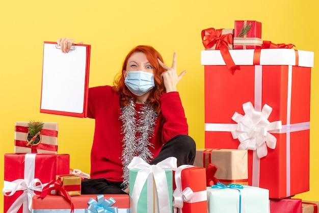 Widok z przodu młoda kobieta siedzi wokół świątecznych prezentów z notatką pliku na żółto