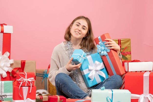 Widok z przodu młoda kobieta siedzi wokół świątecznych prezentów