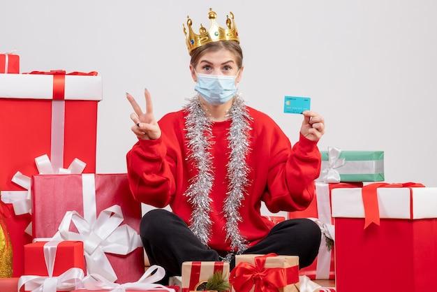 Widok z przodu młoda kobieta siedzi z prezentami świątecznymi trzymając kartę bankową
