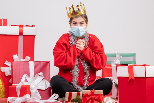 Widok z przodu młoda kobieta siedzi z prezentami świątecznymi w masce i koronie