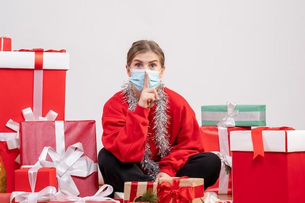 Widok z przodu młoda kobieta siedzi z prezentami świątecznymi w masce