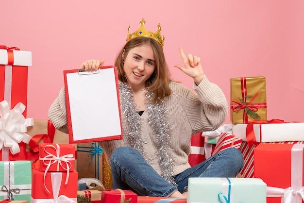 Widok z przodu młoda kobieta siedzi z prezentami z notatką w dłoniach
