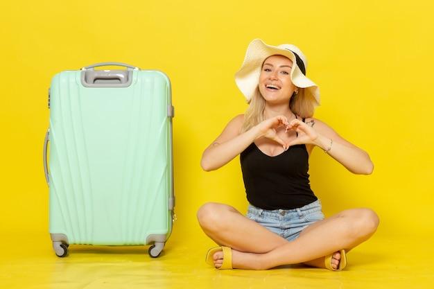 Widok z przodu młoda kobieta siedzi z zieloną torbą i czuje się szczęśliwa na żółtej ścianie wycieczka wakacje podróż słońce podróż dziewczyna