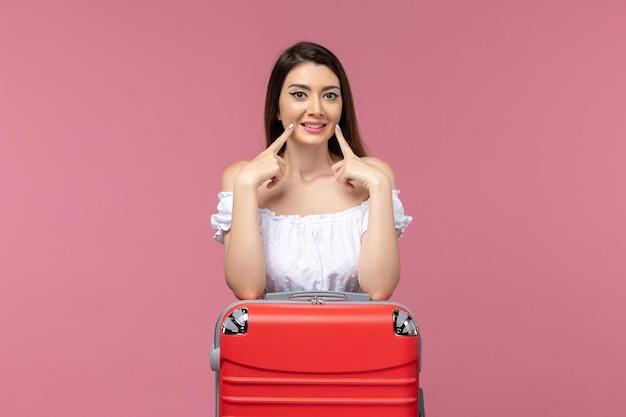 Widok z przodu młoda kobieta stojąca i przygotowuje się do wakacji na różowym tle podróż wycieczka morska kobieta za granicą wakacje