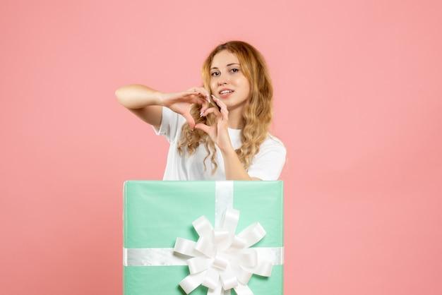 Widok z przodu młoda kobieta stojąca wewnątrz niebieskiego pola prezent wysyłając miłość