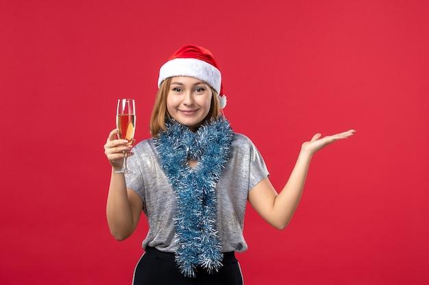 Widok z przodu młoda kobieta świętuje nowy rok na czerwonej ścianie wakacje kolor boże narodzenie
