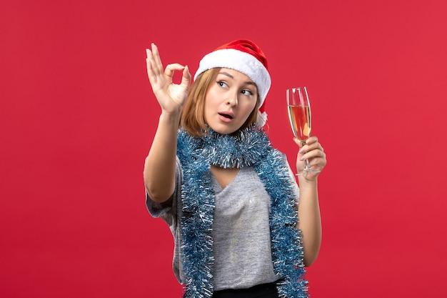 Widok z przodu młoda kobieta świętuje nowy rok na czerwonym tle świąt bożego narodzenia