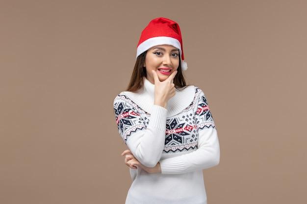 Widok z przodu młoda kobieta szeroko uśmiechnięta na brązowym tle nowy rok emocje boże narodzenie