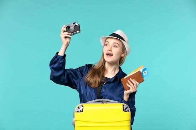 Widok z przodu młoda kobieta trzyma aparat i bilety na jasnoniebieskim tle podróż morska podróż podróż samolotem