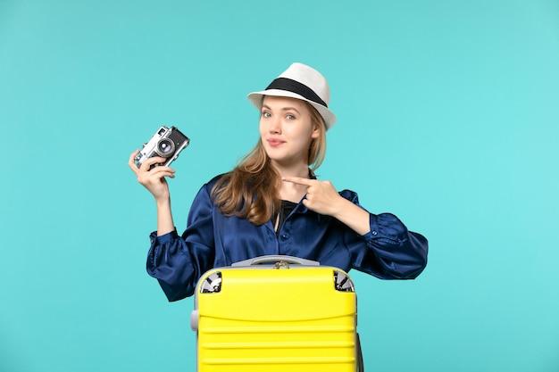 Widok z przodu młoda kobieta trzyma aparat i przygotowuje się do podróży na niebieskim tle wakacje podróż podróż samolotem morze