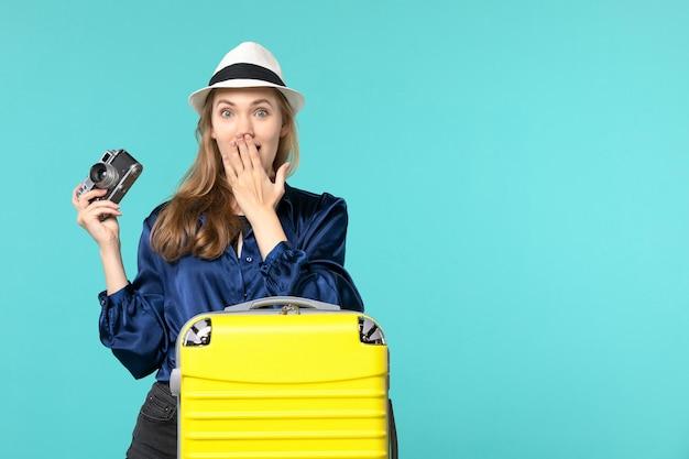 Widok z przodu młoda kobieta trzyma aparat i uśmiecha się na niebieskim biurku kobieta podróż samolotem podróży morskiej