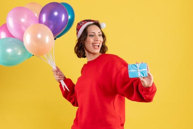 Widok z przodu młoda kobieta trzyma balony i mały prezent na żółte święta bożego narodzenia kobieta emocji nowego roku